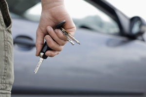 Close up of a man holding car keys and a car in the background